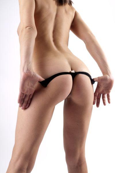 Frau zieht schwarzen Tanga aus