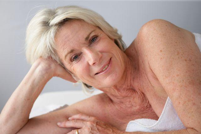 Ältere blonde Frau mit Handtuch