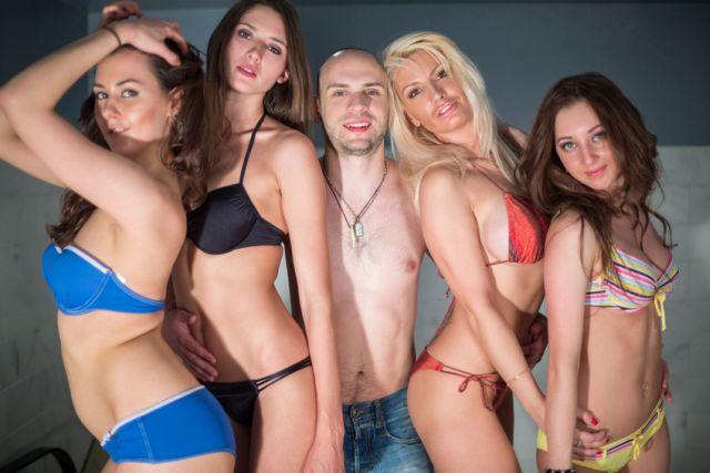 Mann mit vier Frauen in Bikinis