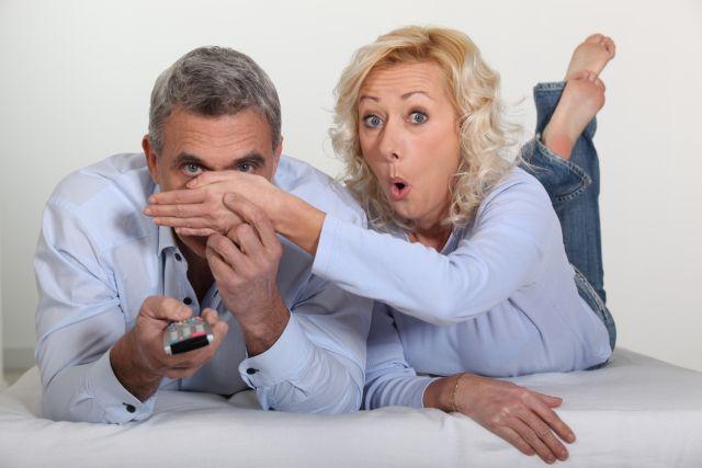 Frau hält dem Mann beim Fernsehen die Hand vor die Augen