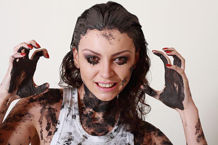 Frau mit Schlamm im Gesicht