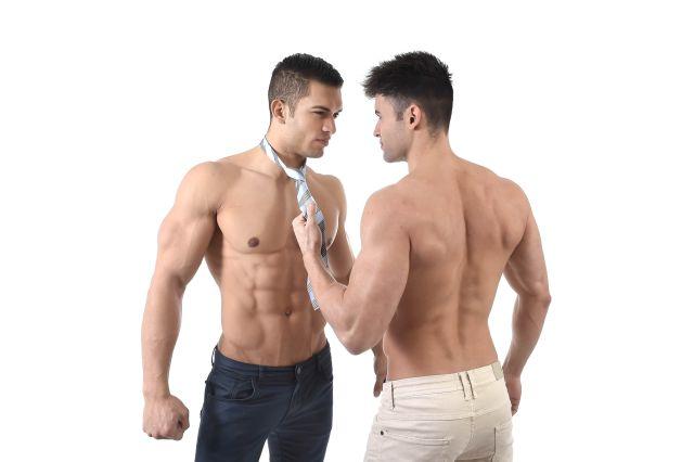 Zwei Männer mit nacktem Oberkörper flirten miteinander