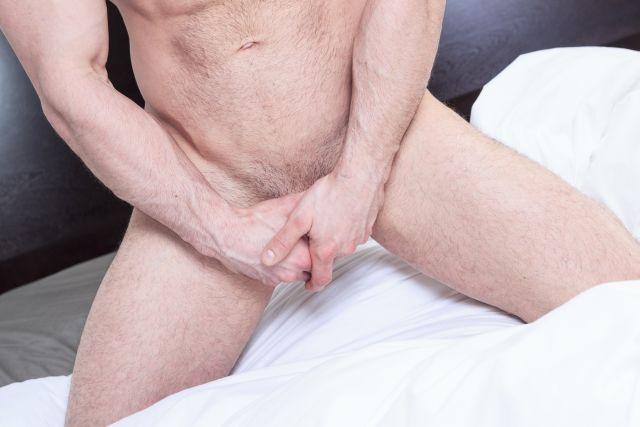 Nackter Mann verbirgt sein Geschlechtsteil mit den Händen