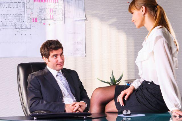 Sekretärin sitzt vor Chef auf dem Schreibtisch