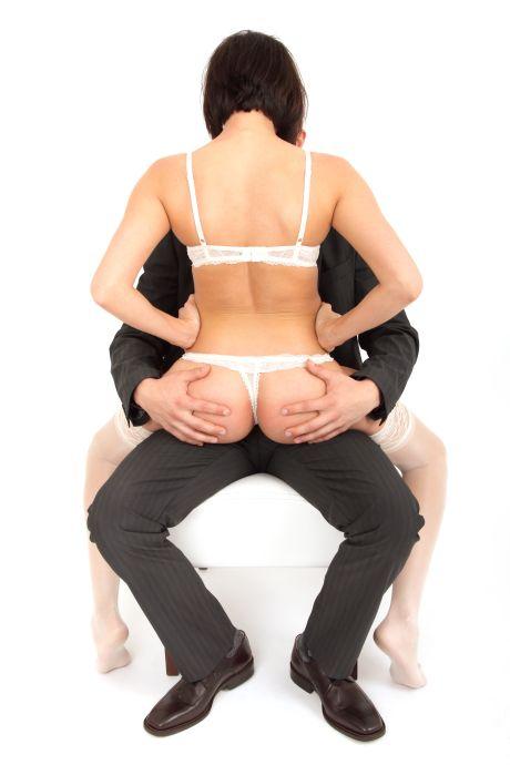 Frau im Stringtanga und langen weißen Strümpfen sitzt auf Mann im Anzug