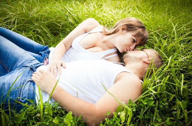 Ein sich küssendes Paar auf der Wiese