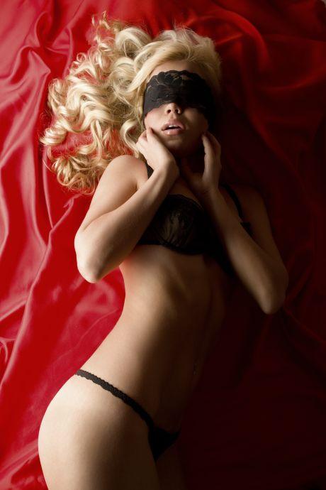 Leidenschaftliche Blondine mit verbunden Augen in verführerischer Pose