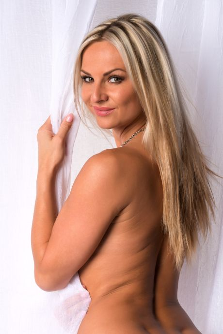 Sexy blonde Frau lächelt in die Kamera