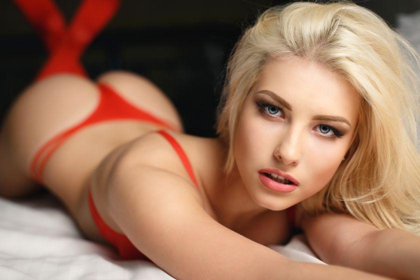 Blonde Frau liegt in roter Wäsche auf dem Bett