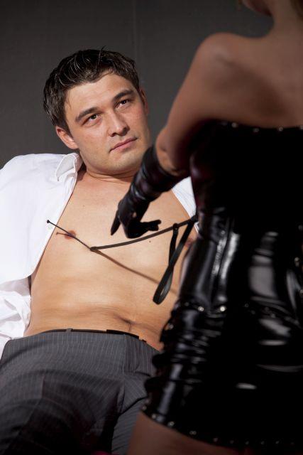 Domina tippt einem Mann mit Gerte an die Brust