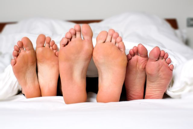 Drei Füße ragen unter der Bettdecke hervor