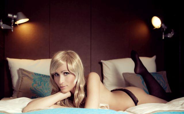 Blonde junge Frau liegt im Tanga auf dem Bett