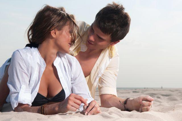 Heißes Paar liegt im Sand und schaut sich an