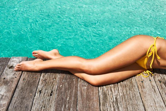 Sexy weibliche Beine am Strand
