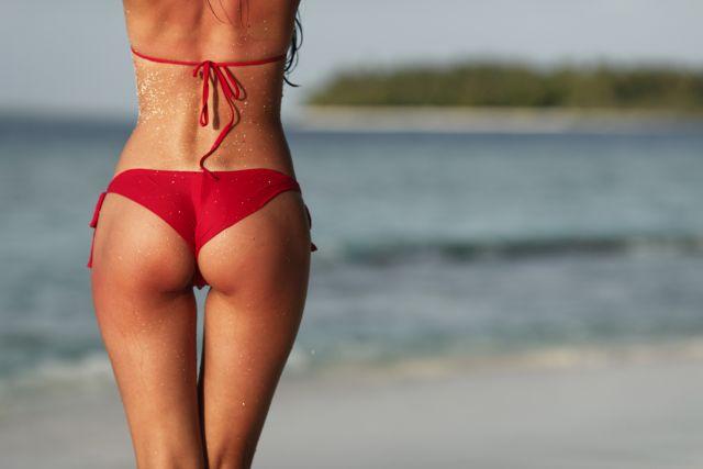 Frau in Bikini von hinten am Strand