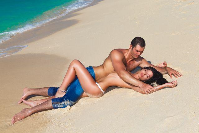 Frau und Mann halbnackt liegend auf dem Strand