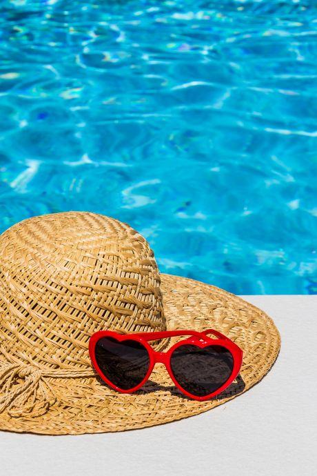 Hut mit Sonnenbrille am Pool