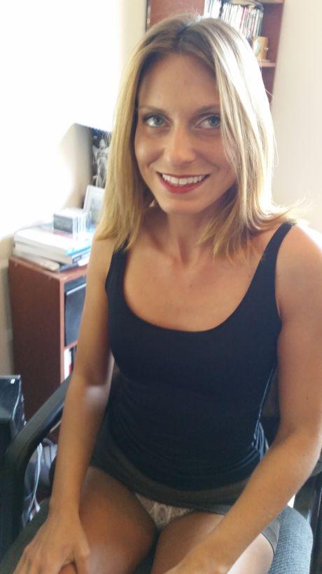 Blonde Frau im schwarzen Top und weissem Höschen lächelt