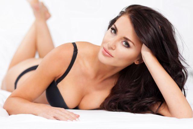 Attraktive Frau in Unterwäsche auf einem Bett