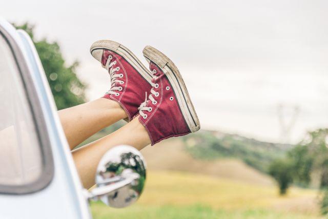 Beine aus einem Auto mit roten Turnschuhen