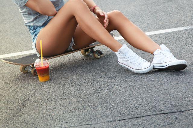 Frau mit Sneakers auf einem Skateboard