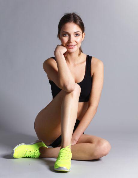 Sportliche junge Frau in Neon-Sneakern