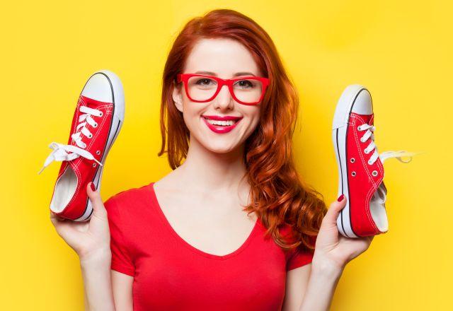Rothaarige Frau hält Sneakers in die Luft