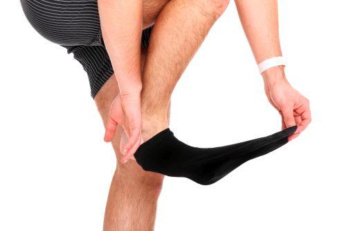 Mann zieht Socken aus