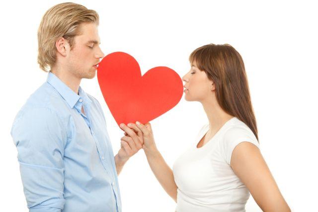 Blonder Mann und brünette Frau halten Herz