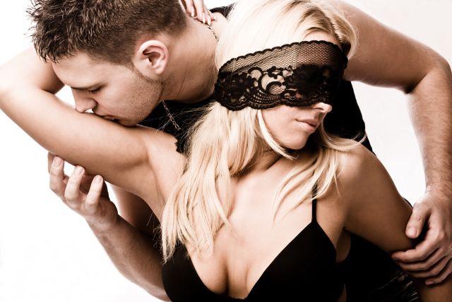 Mann verführt leichtbekleidete Frau mit verbundenen Augen