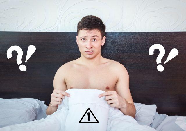 Mann sitzt im Bett und zeigt unter die Bettdecke