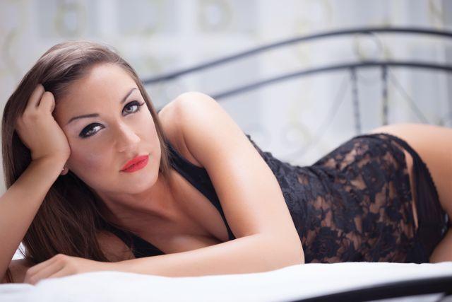 Junge Frau liegt in schwarzer Lingerie auf einem Bett und schaut den Betrachter auffordernd an.