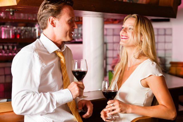 Mann und Frau trinken ein Glas Rotwein an einer Hotelbar