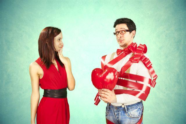 Pärchen, sie im roten Kleid, er mit roter Schleife umwickelt und Herzchen in der Hand