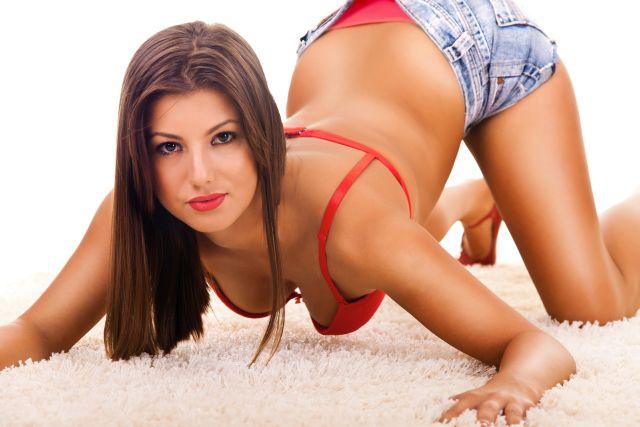 Fru in rotem BH und knapper Jeans räkelt sich auf Teppich