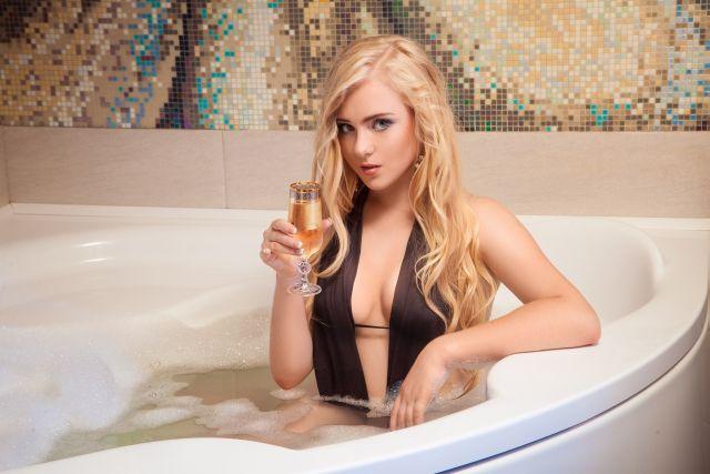 Blonde Frau sitzt mit Sektglas in der Badewanne