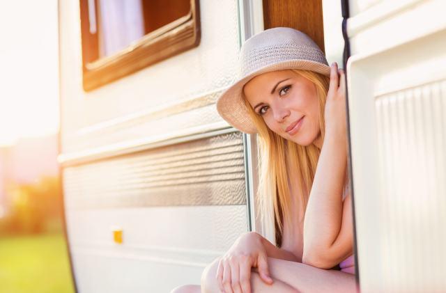 Junge Frau schaut aus dem Wohnmobil raus