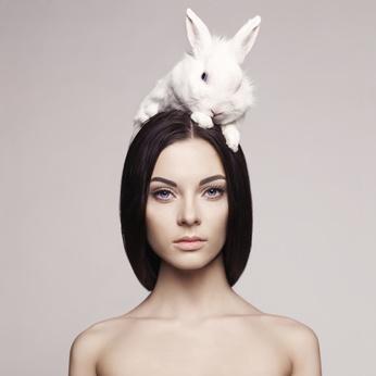 Hübsche Frau mit weißem Kaninchen auf dem Kopf