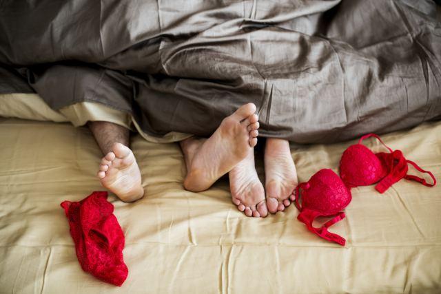 Füße eines Pärchens schauen unter der Bettdecke hervor