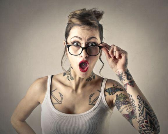 Frau mit Tattoos schaut hinterfragend
