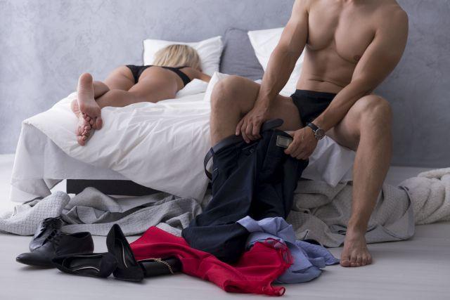 Mann zieht sich an nach dem Liebesspiel, Frau liegt mit Bauch auf Bett