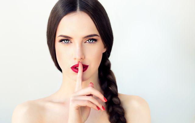 Frau hält ihren Finger vor den Mund