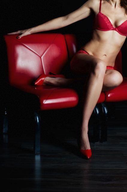 Frau in roten Dessous posiert auf roter Bank