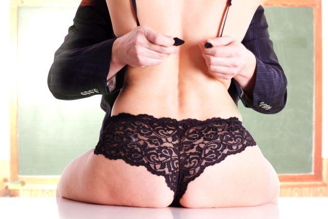 Weiblicher Rücken umfasst von zwei Männerhänden