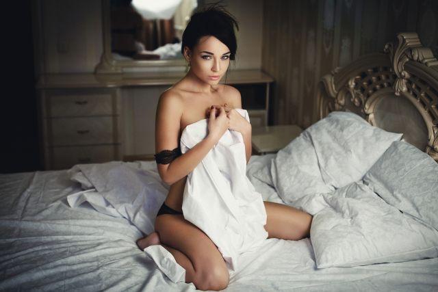 sexy Brünette posiert auf Bett