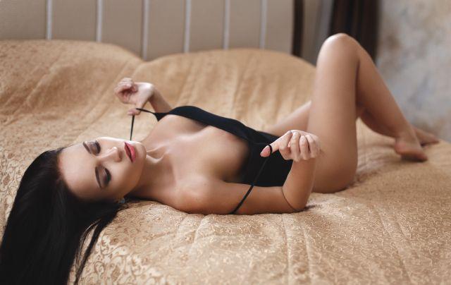 Frau posiert in Reizwäsche auf Bett