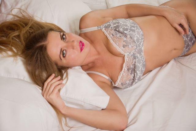 Sexy Blondine in Dessous auf ihrem Bett
