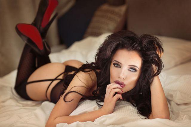 verführerische Brünette in Unterwäsche und High Heels im Bett