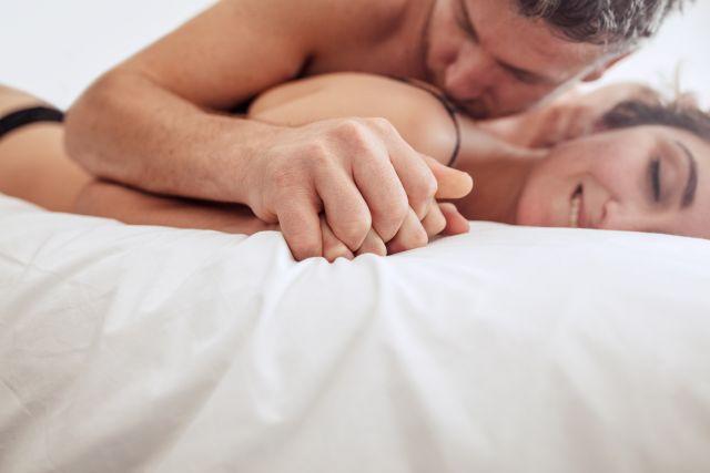 Mann liegt auf der Frau und küsst ihre Schulter