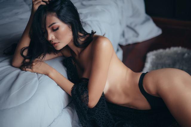 schöne dunkelhaarige Frau posiert in Slip liegend